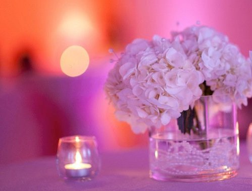 An image of white flowers and candles on the table